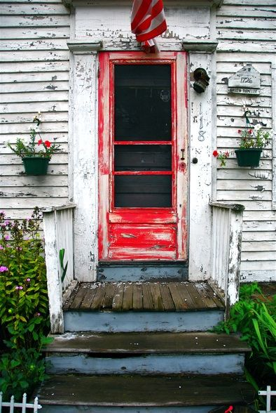 Shabby house, with red door, and blue steps.