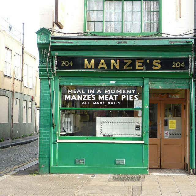 Manze's, Deptford SE8    Meat Pies: Meal In A Moment    There are a few Manze's around London but they are not all run by the same company. Several brothers who had come to London from Italy opened pie & mash shops and by 1930 there were a total of 14 shops in London bearing the Manze name.There are two pie & mash shops in Deptford High Street, the other is Goddard's opposite, which didn't get photographed as there was a car parked infront.