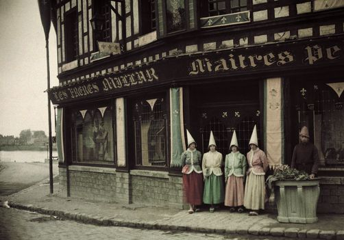 Compiegne, Oise. People stand in front of a reconstructed shop of a master painter. Photographer: JULES GERVAIS COURTELLEMONT