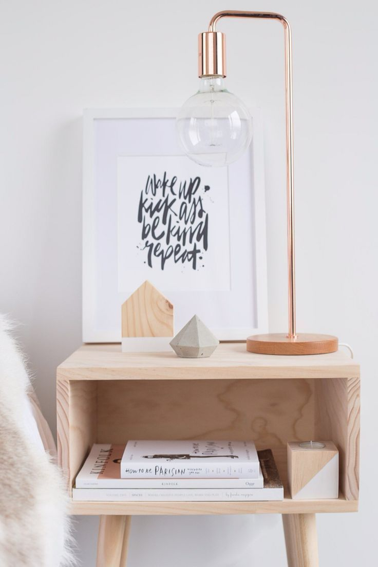 styled modern nightstand with copper lamp, brush lettered artwork and simple accessories