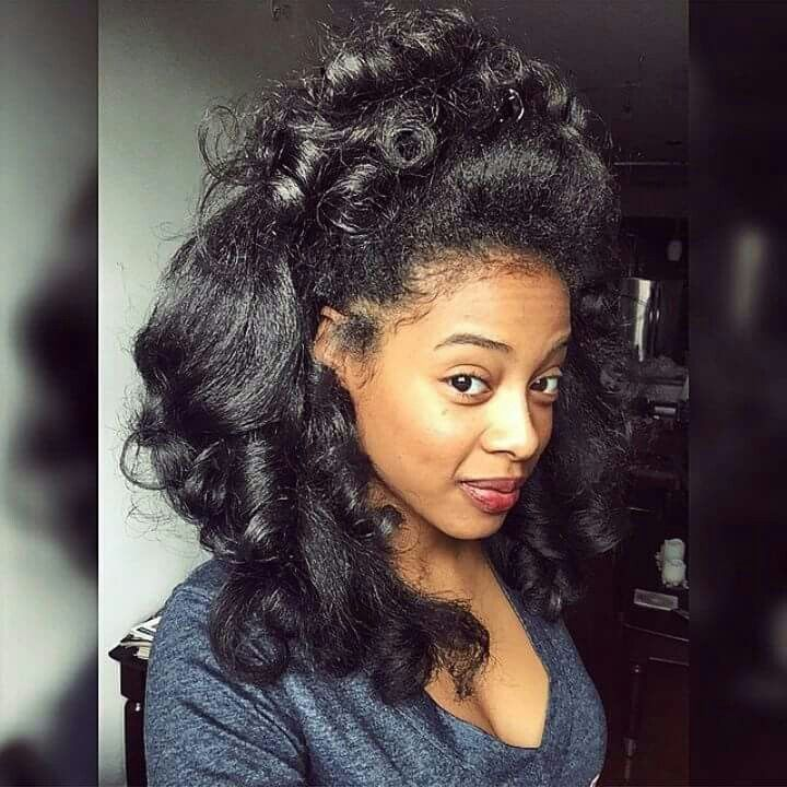 Looks like a pinned up roller set on long natural hair or maybe a curling iron