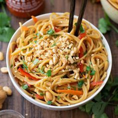 20 Minute Spicy Thai Noodle Bowls Recipe Main Dishes with spaghetti, vegetable oil, sesame oil, soy sauce, rice vinegar, Sriracha, peanut butter, honey, garlic, green onions, red bell pepper, carrots, cilantro, dry roasted peanuts, crushed red pepper flakes, sesame seeds