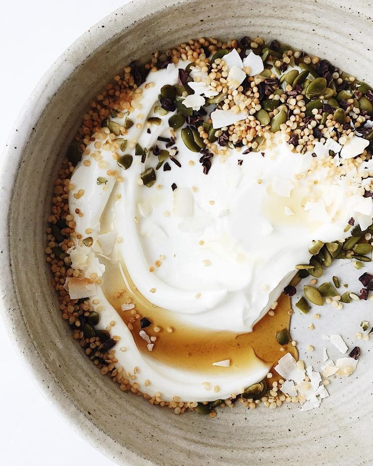 Plain Greek yogurt over pumpkin seeds, puffed quinoa, coconut, and cocoa nibs with a swirl of pure maple syrup