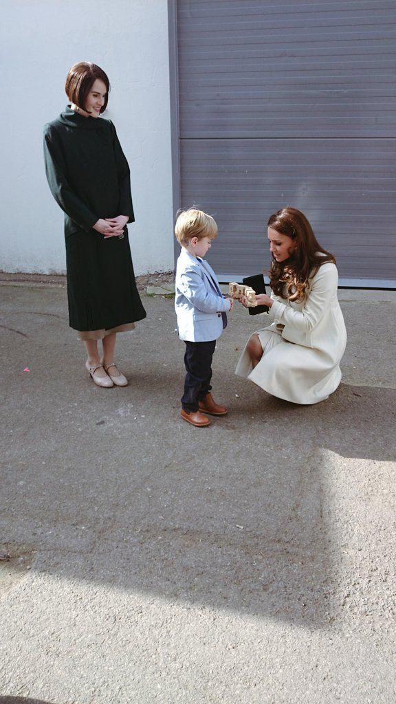 """George hands The Duchess a wooden train for Prince George #DuchessAtDownton @EalingStudios"""