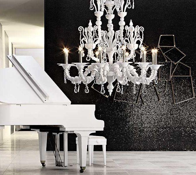 Hoe creëer je een sfeervol klassiek zwart-wit interieur?   Geraffineerd zwart met luchtig wit zorgt voor een uniek contrast, kijk eens hoe mooi de witte candalier van Barovier & Toso uitkomt op de elegante zwarte achterwand van Casamood vetro kleur carbone lux.