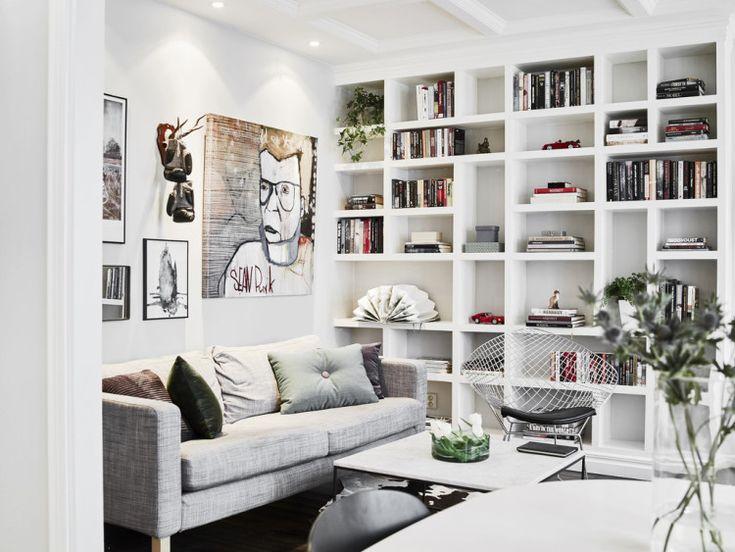 Living room: built-in bookshelves, white walls, white coffered ceiling, IKEA KARLSTAD Isunda grey sofa, mismatched artwork
