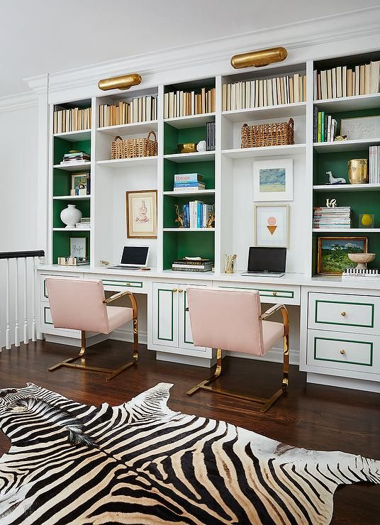Stunning home office features a wall of built-in bookcases, with backs of bookcases painted ...