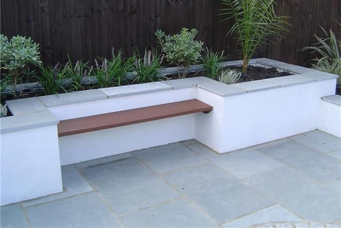 Kota Blue Limestone Paving used in an urban garden. The steel blue/grey colouring of the stone compliments the white rendering and wooden bench perfectly.