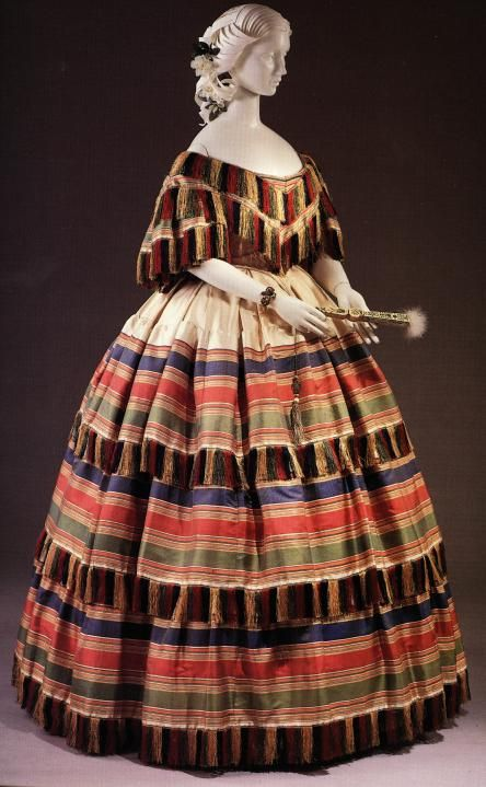 This dress represents the plaid trend of the time period. Produced in the mid 1800s, this dress is made of silk and wool. Additionally, the off the collar look is typical of the crinoline period.