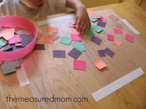 How to keep a 1 year old busy -- cut a sheet of clear contact paper and tape it to the table STICKY SIDE UP.  Give tot scraps of construction paper to stick to the contact paper.  Great first craft and can be done independently with almost no mess!