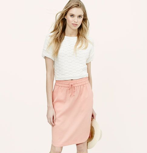 "Add a sportif twist to your skirt routine with a jogger-styled piece. Elasticized drawstring waist. Slash pockets. Back welt pockets. Shirttail hem. 23"" long."