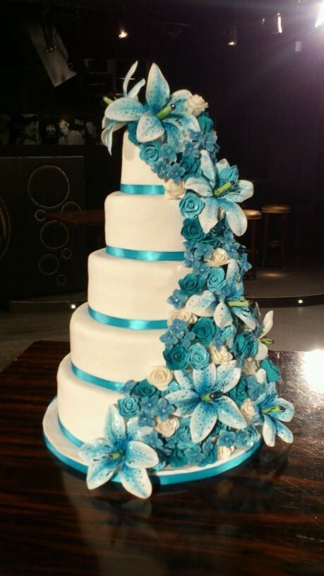 Teal and White Wedding cake with cascading flowers.  Keywords:  #teathemedweddinginspirationandideas #tealweddingcake #jevelweddingplanning Follow Us: www.jevelweddingplanning.com  www.facebook.com/jevelweddingplanning/ #TealWeddingIdeas