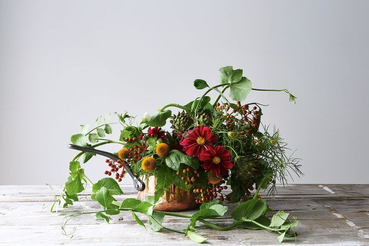 """""""For a rustic design, I love to add lots of edibles to the pot. These beautiful copper pans double as elegant vases. This design is meant to evoke an old stone farmhouse in Provence, where wild game cooks on a spit nearby.    In this arrangement:      Echinacea     Pea pods on the vine     Cosmos     Artichokes     Viburnum berries -- Emily Thompson Flowers"""