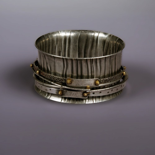 Connie Fox  The shape of the cuff creates interest but it is also functional. The cuff pattern is repeated to give unity to the design. The small bangles give rise to movement and sound. Connie Fox. http://www.blogtalkradio.com/whaleystudios/2015/02/12/metalsmith-benchtalk-with-local-author-and-jewelry-designer-connie-fox