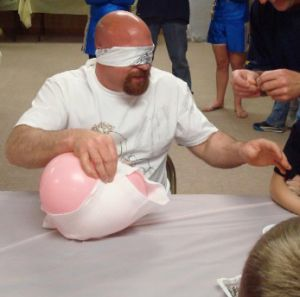 Blind folded diapering with safety pins. Don't pop the balloon!! Baby shower games pic.