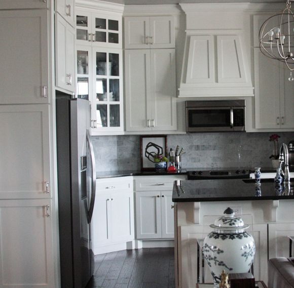 white cabinets with some glass doors, marble tile backsplash, dark floors, pendants.  I also love the white and grey chinoiserie vase in the foreground.