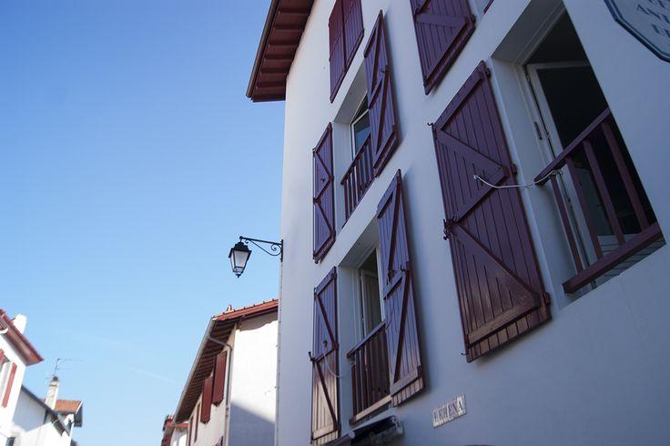 Los postigos rojos de las ventanas en San Juan de Luz (Francia) a la luz de agosto.