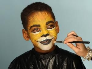 To give your child a ferocious lion's face for Halloween, simply paint a basic orange and yellow face. Then paint their top lip black and extend curving line up cheeks slightly. Paint their bottom lip black, then add black dots to white area above top lip. Add whiskers by brushing white paint in small, short strokes around mouth and cheek area. Add a line of black paint under eyes, angling down the nose to create those striking big-cat eyes. Use a blending brush and brown eye shadow to shade…