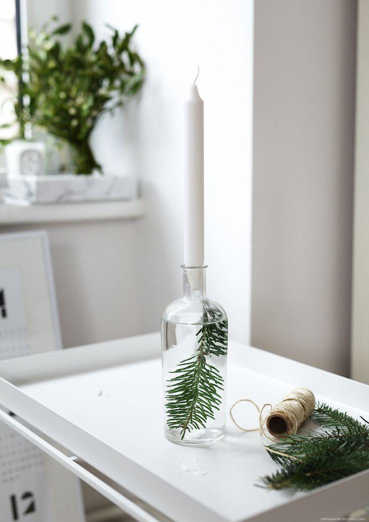 Un joli DIY facile à réaliser en famille pour créer une ambiance de Noël féerique : transformer une bouteille en verre transparente en bougeoir, la remplir d'eau, y glisser une branche de sapin, visser une bougie blanche, et hop! une déco temporaire de bon goût et récup #decoration #noel #minimaliste