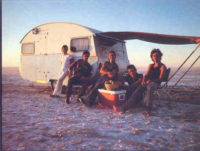 Cold Chisel with the 1960s Globetrotter caravan used for their Circus Animals album cover.  They abandoned the van there.  Lake Eyre, South Australia. Summer 1981/82.