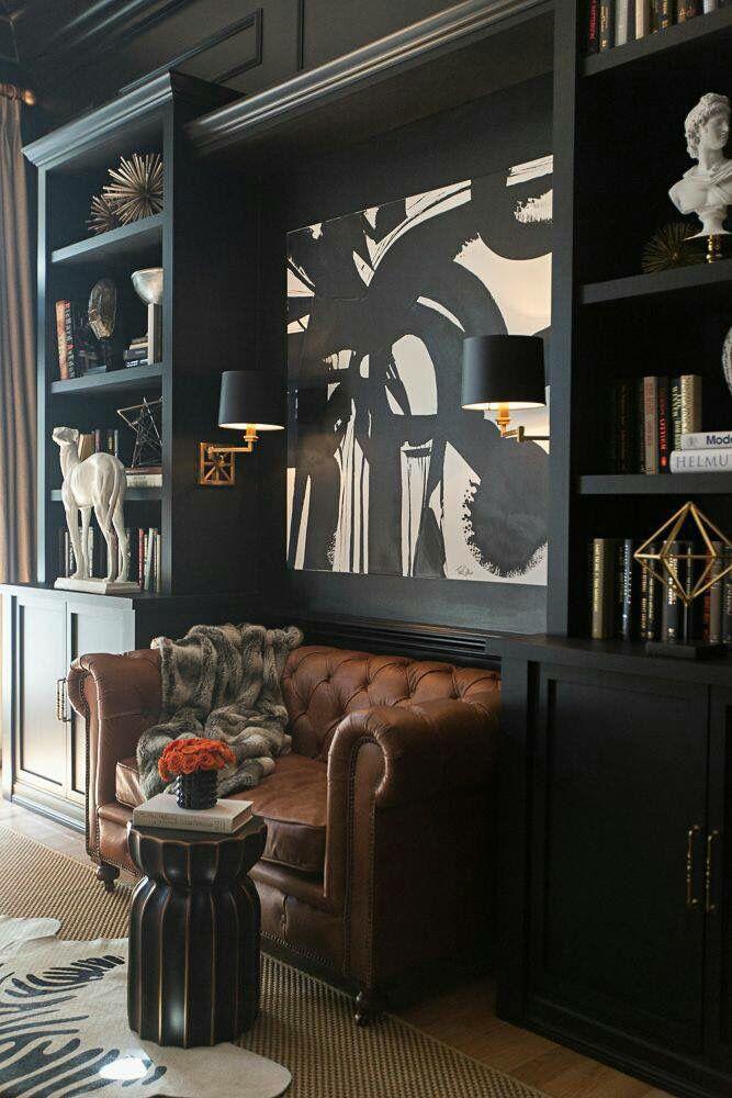 Black bookshelves and tan Chesterfield
