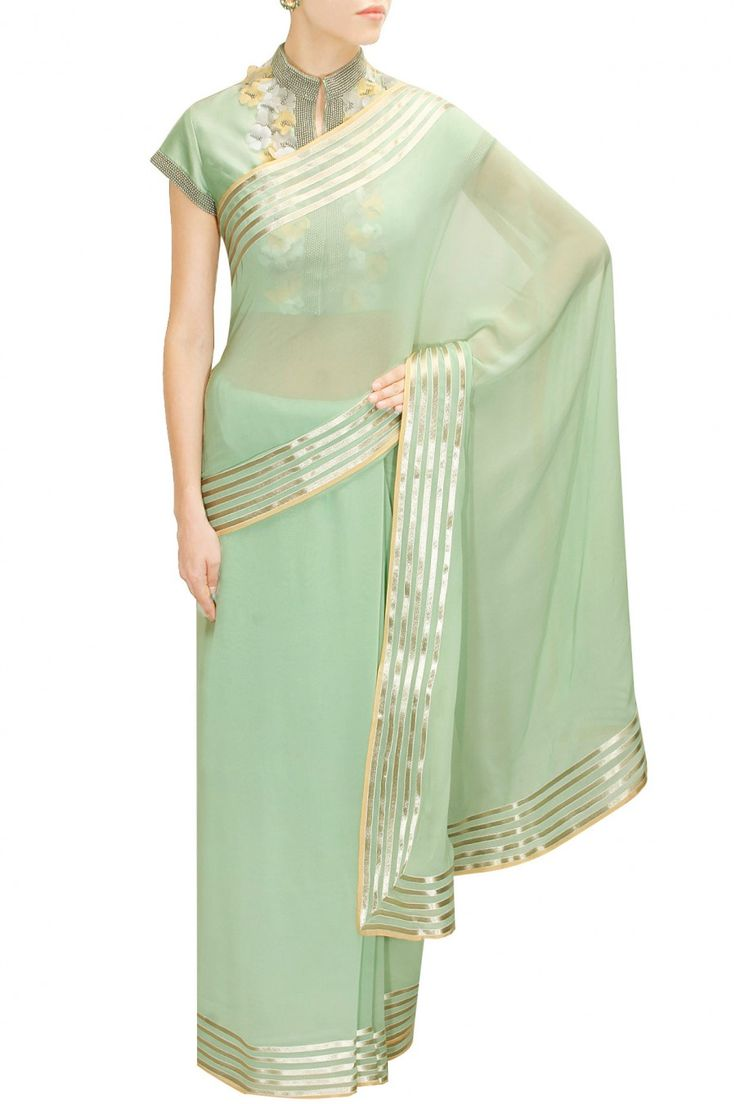 Pastel green striped border sari with flower embroidered blouse by Ilk by Shikha and Vinita.  Shop at: http://www.perniaspopupshop.com/designers/ilk-by-shikha-and-vinita