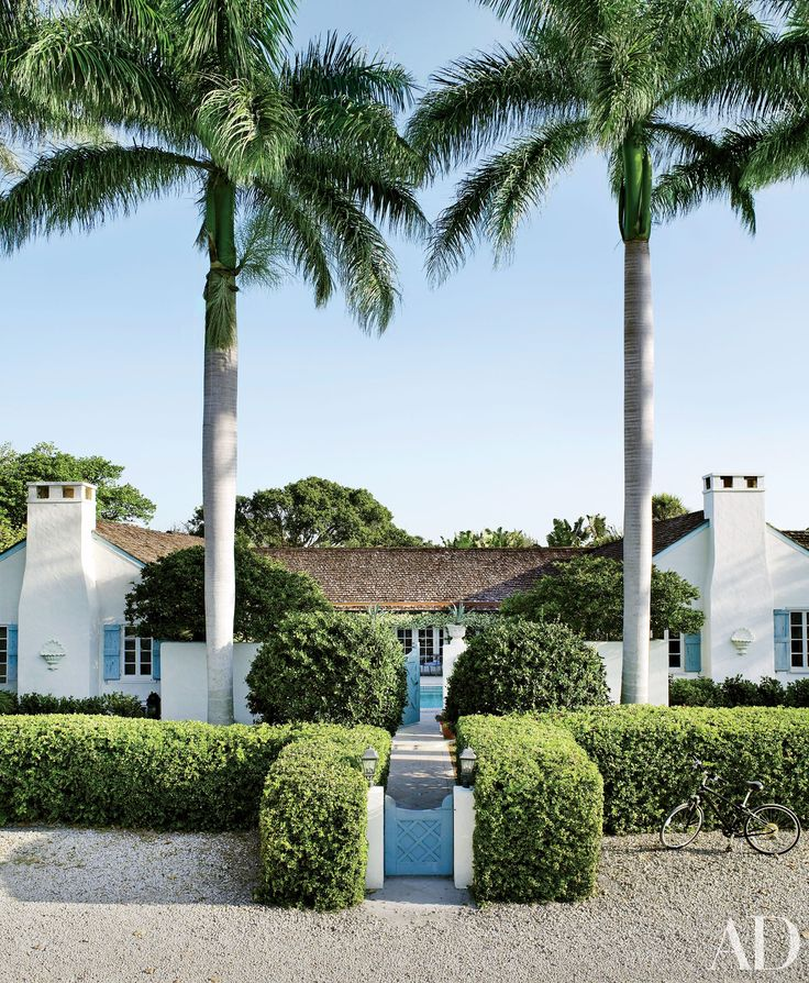 This Florida home pulls inspiration from its tropical and beach surroundings, with an etherial white facade, accented by blue finishings and lush hedges. | archdigest.com