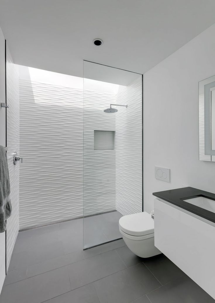 Grey floor tiles have been paired with textured white tiles to create a contemporary bathroom, while a skylight located above the shower adds a touch of natural light to the space. #ModernBathroom #WhiteAndGreyBathroom #BathroomDesign