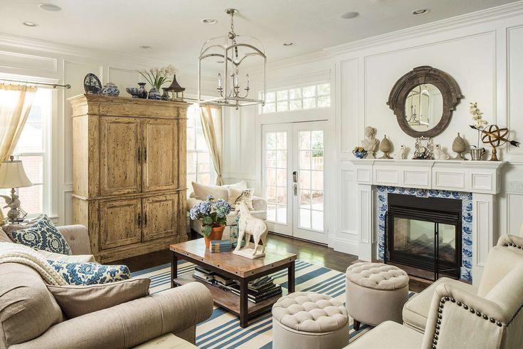 Traditional decor in a living room with tall armoire and blue accents. Design by The Fox Group. #livingroomdecor #tmeless #traditionalhomedecor #classicdesign #interiordesigninspiration