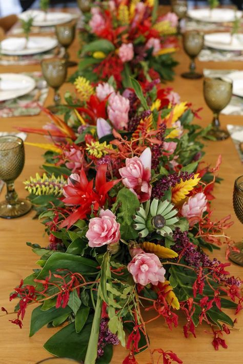 Nossa mesa decorada com arranjos feitos de alpínia, nos tons de rosa e vermelho; semente de Santa Bárbara; ócna; bromélia; semente de urtiga; e helicônia biquinho. Arranjo único de centro de mesa.