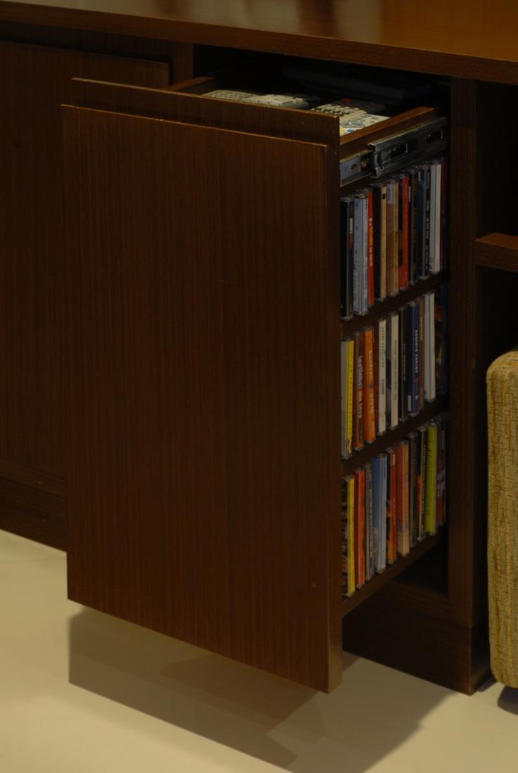 Organização na sala de TV: gavetão vertical para CDs e DVDs nas laterais e em cima apoio para controles remotos.