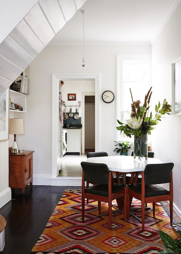 love the combination of the bright geometric rug, white walls, and dark floor.