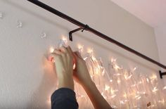 Headboard made from sheer curtains and lights.