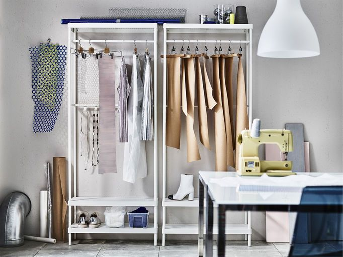 A sewing room with two white coat racks and built-in shoe storage, shown with trouser hangers holding cut-out clothes patterns and clothes hangers with blouses and dresses.