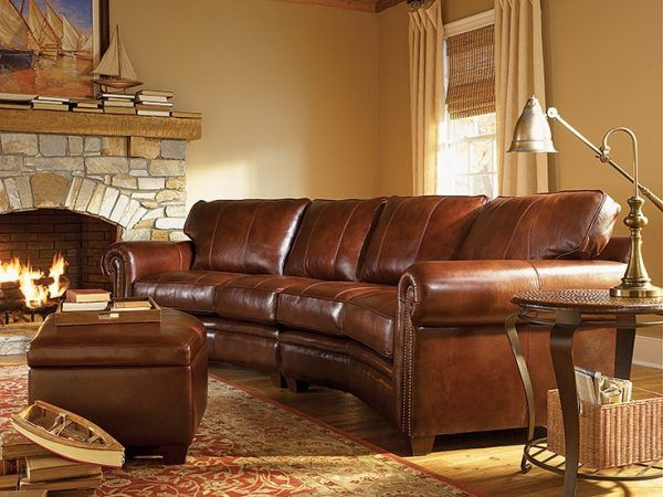 rustic leather living room furniture using curved sectional sofa and ottoman coffee table above oriental area rugs wool nearby stone mantel fireplace