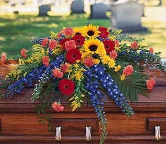 Funeral casket spray with sunflowers, gerber daisies, carnations, blue delphinium and foliage.