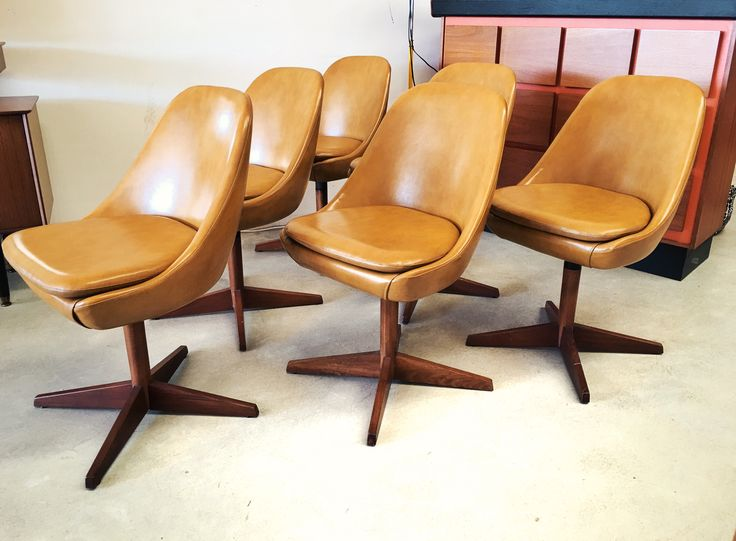 Set of swivel pod shape dining chairs by th brown on a