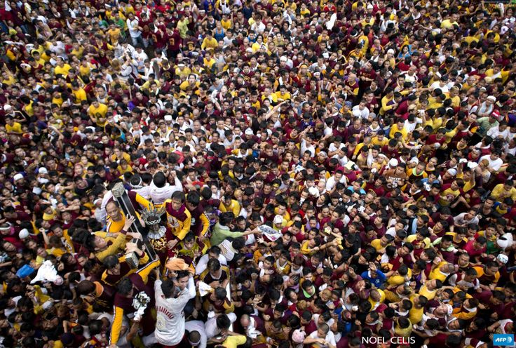 PHILIPPINES, Manila : TOPSHOT - Devotees join the annual procession with  the religious icon of the Black Nazarene (bottom-L) in Manila on  January 9, 2016. Barefoot men and women in search of miracles hurled  themselves above huge crowds to touch a centuries-old icon of Jesus  Christ as one of the world's largest Catholic festivals got under way.  AFP PHOTO / NOEL CELIS