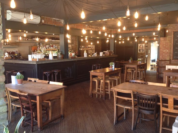 Lights of Alice house. Light up! Vintage tables. Wooden floors. Cement bar top. Library. Weddings