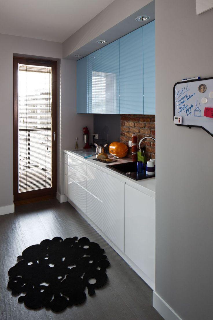 Mała kuchnia w bloku  została tak urządzona, aby wszystko było pod ręką. Spokojne barwy – biały, szary i niebieski – ożywiają dodatki w energetycznych kolorach, a cegła nad blatem w kuchni ciekawie koresponduje z taką samą w salonie.