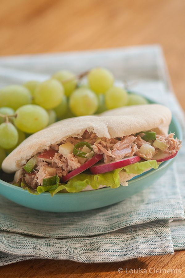 Tuna salad with green onions and diced apple in pita pockets.