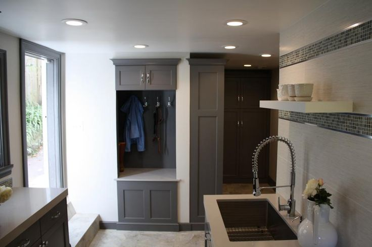 This mudroom offers residents a place to hang coats and store boots as well as a sink to rinse hands or gardening tools. The gray and white color palette keeps the feel crisp and stylish.