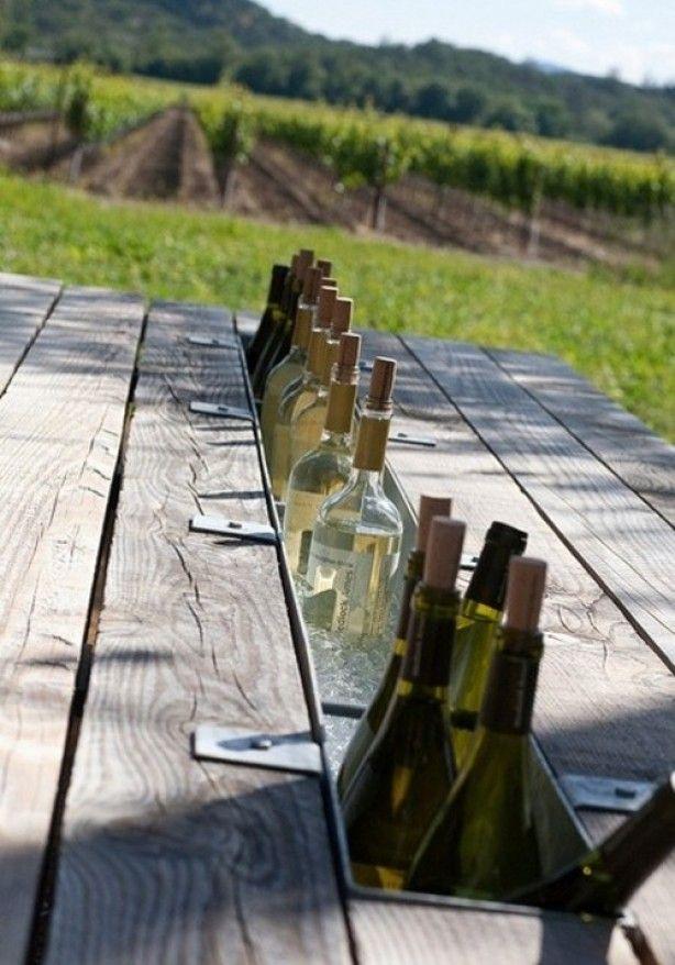 Tuintafel. Verwijder de middelste plank en monteer zinken plantenbakken dat dient als flessenkoelers.
