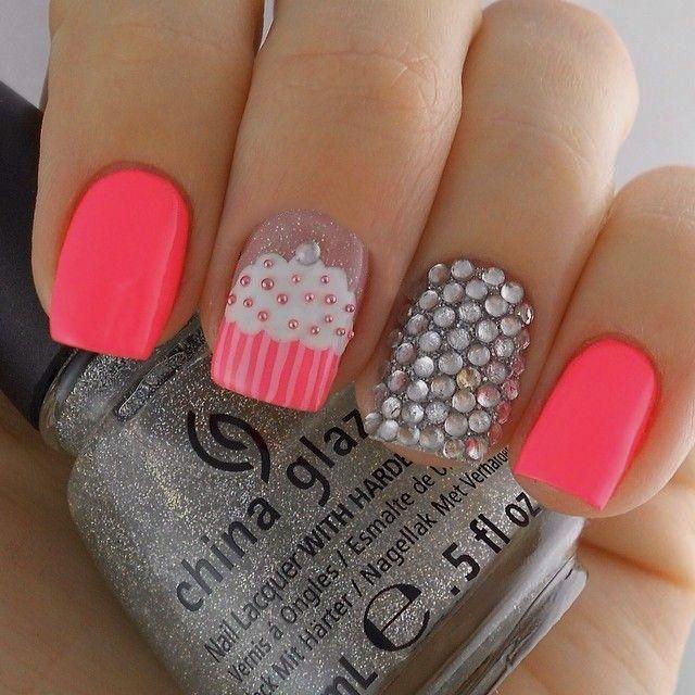 uñas decoradas con esmalte color rosa, piedras y un pastelillo dibujado