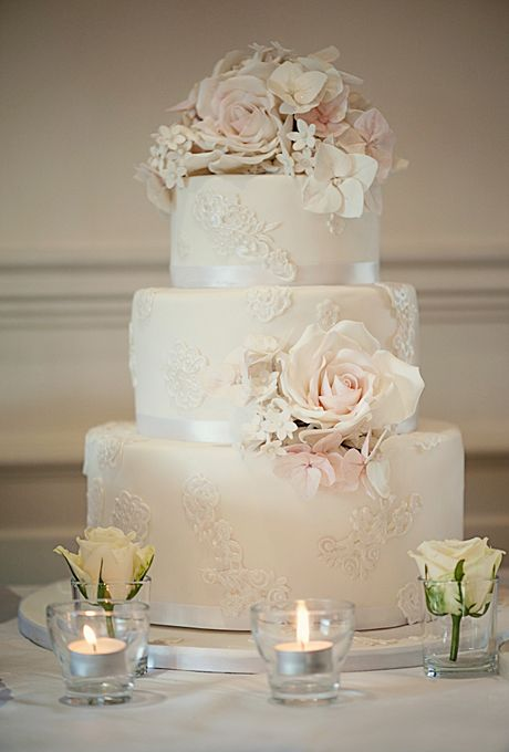 Brides.com: . A three-tiered wedding cake by Elizabeth's Cake Emporium was decorated with sugar blossoms and lace appliqués.