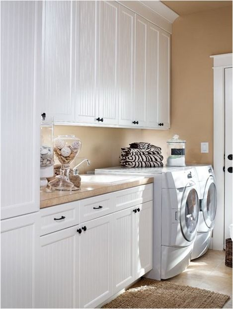 """Pretty laundry room with white cabinets and """"Filbert"""" paint on the walls by Miller Devine"""