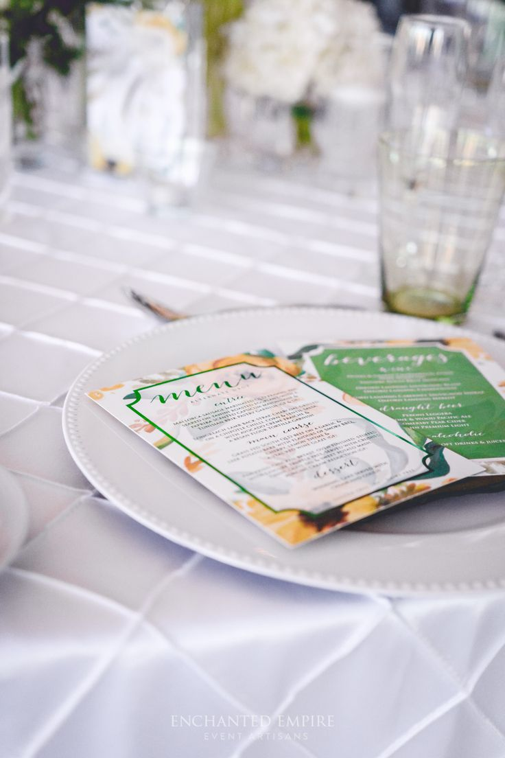 A crisp base of perfectly white pintuck floor length linen this modern botanical wedding was styled incorporating stunning whites with botanical greens. Textured willow pintuck napkins placed atop beaded white charger plates, complimented by forest green glassware. Touches of yellow subtly incorporated in the hand painted table numbers perfectly matching with the custom designed menus with stunning emerald green foiled print. YouTube: https://www.youtube.com/watch?v=aaYN11o4vIE