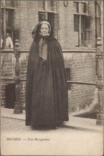 Portret van een Brugse vrouw. De foto werd gemaakt op de Blinde-Ezelbrug. De vrouw is gehuld in kapmantel en draagt een pijpenmuts.