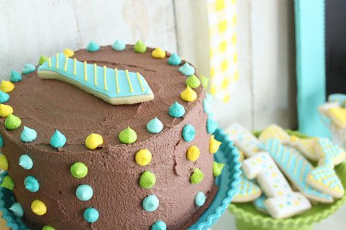 little man bow tie and mustache theme birthday party in blue yellow and green chocolate smash cake with necktie