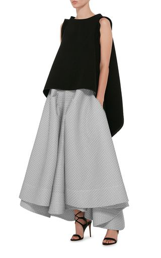 An authority on eveningwear in his native Australia, the Sydney-based designer lets loose on technical fabrics and sculptural silhouettes this season. This **Maticevski** skirt features a high rise with a fitted waistband, pleated panels extending from the sides, and a midi length draped hem.